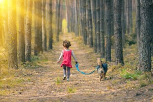 Cchild walking at the forest with her dog